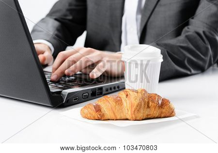 Busy businessman has breakfast coffee and croissant pastry waiting while typing on laptop working