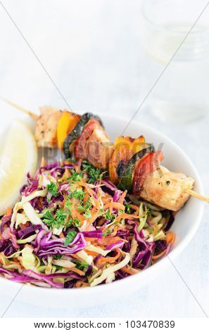 Barbecue chicken kebabs on wooden skewer sticks served with raw side salad coleslaw made of shredded cabbage and carrot