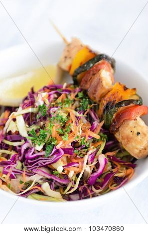 Barbeque chicken kebabs on wooden skewer sticks served with raw side salad coleslaw made of shredded cabbage and carrot