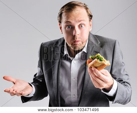 Busy businessman eating takeaway sandwich on the go, shrugging to the fast pace of life