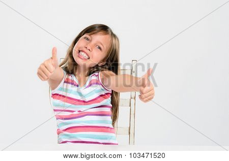 Portrait of a happy girl sitting at a table with thumbs up
