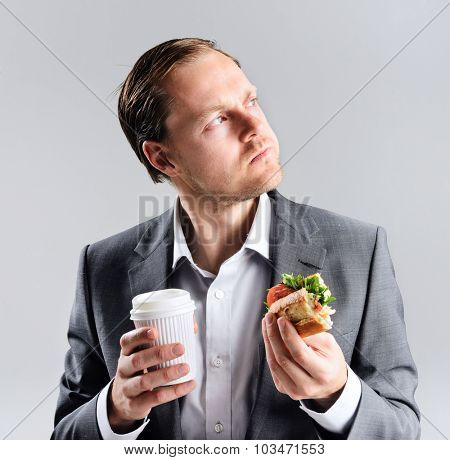 Busy businessman eating takeaway sandwich on the go, rushing through lunch break