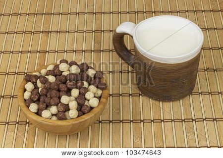 Chocolate cereal balls in a bowl of bamboo. Healthy breakfast with fruit and milk.