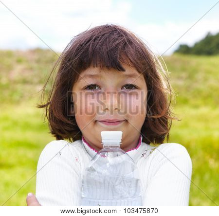 The Child Holds A Bottle With Water