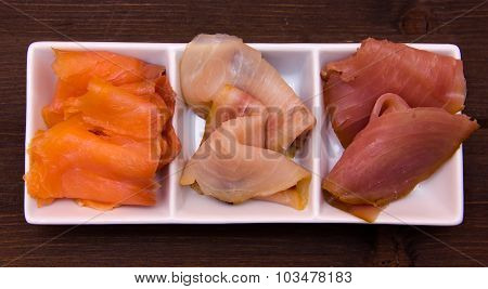 Trio of smoked fish on platter on wood from above