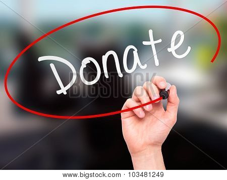 Man Hand writing Donate with marker on transparent wipe board.