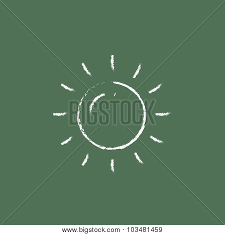 Sun hand drawn in chalk on a blackboard vector white icon isolated on a green background.