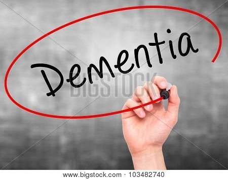 Man Hand writing Dementia with marker on transparent wipe board.