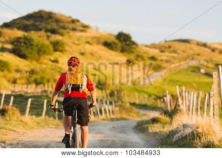 Bicycle riding enduro adventure in sunset summer mountains landscape. Man cycling MTB on rural count