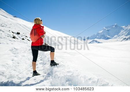 Young happy woman hiker looking at mountain peaks in winter mountains. Hiking and travel inspiration