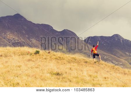 Hiking man and success in mountains. Fitness and healthy lifestyle outdoors in summer nature