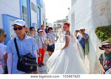 SANTORINI, GREECE - AUGUST 05, 2015: woman in white wedding dress walking on streets of Santorini island. Santorini island popular place for wedding celebrations