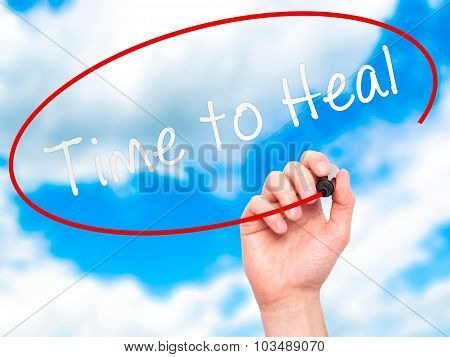Man Hand writing Time to Heal with marker on transparent wipe board.