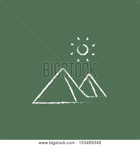 Egyptian pyramids hand drawn in chalk on a blackboard vector white icon isolated on a green background.