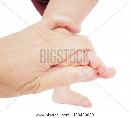 Male Hand Holding Firmly Around A Foot Of Toddler In Air Isolated On White