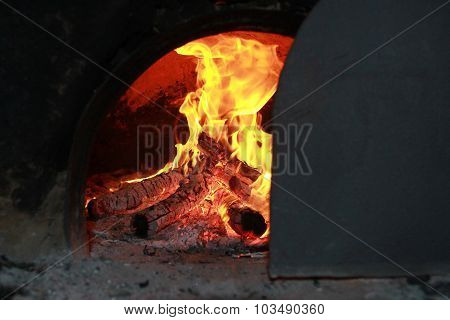 Bright Fire Burning In The Oven Covered With A Door Rail
