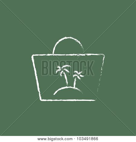 Beach bag hand drawn in chalk on a blackboard vector white icon isolated on a green background.