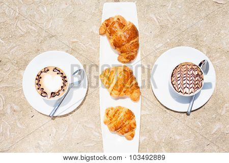 Two Cups Of Coffee With Latte Art And Croissants