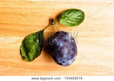 Single Plum Fruit With Green Leaves On Wooden Table