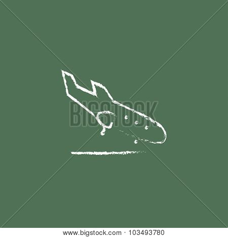 Landing aircraft hand drawn in chalk on a blackboard vector white icon isolated on a green background.