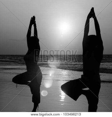 Serene People In The Beach Doing Yoga In The Sunset Concept