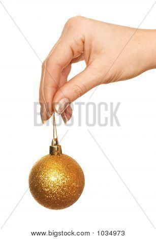 Hand Holding Gold Christmas Ball