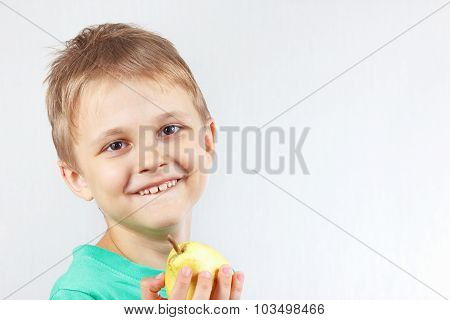 Little funny boy in green shirt with yellow juicy pear