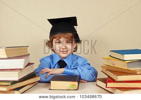 Little boy in academic hat among old books