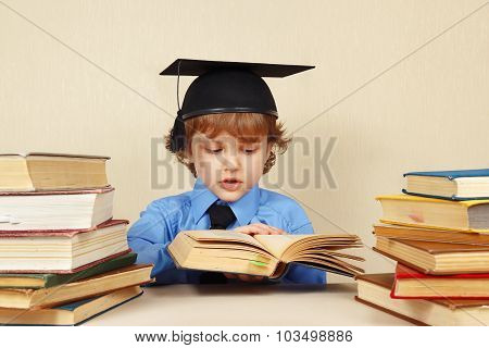 Little smart boy in academic hat turns the pages of old book
