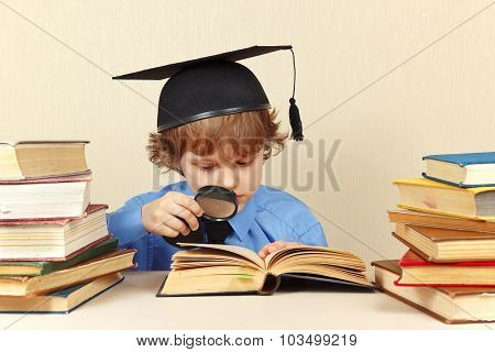 Young boy in academic hat studies an old books with loupe