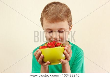 Little boy with bowl of fresh sweet strawberries