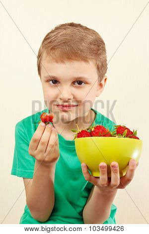 Little boy eating sweet red strawberries from bowl