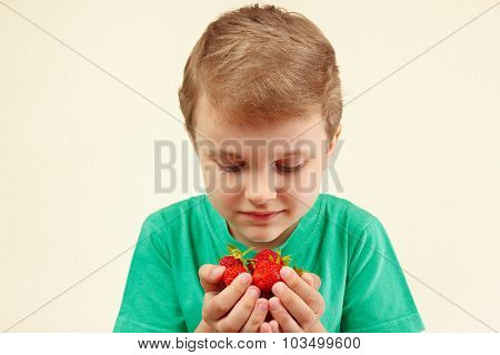 Young boy holds handful of fresh ripe strawberries