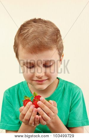 Little boy holds handful of sweet strawberries