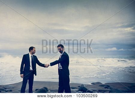 Businessmen shaking hands with stormy ocean background.