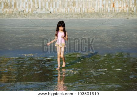 Little Asian Girl Walk From The Beach To The Sea