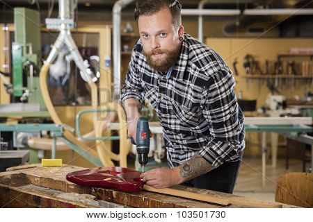 Man working at workshop with guitar