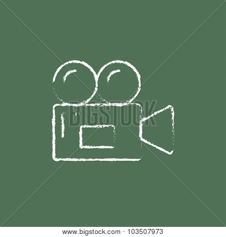 Video camera hand drawn in chalk on a blackboard vector white icon isolated on a green background.