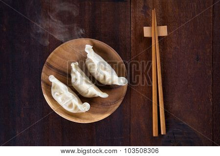 Top view fresh dumplings with hot steams on wood plate with chopsticks. Chinese meal on rustic old vintage wooden background.