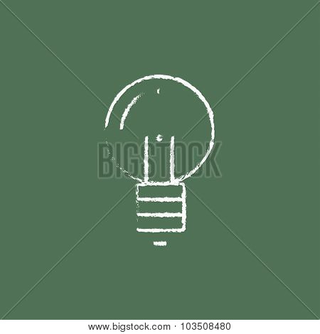 Light bulb hand drawn in chalk on a blackboard vector white icon isolated on a green background.