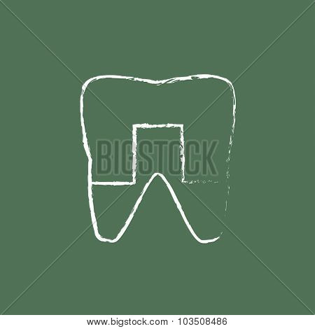 Crowned tooth hand drawn in chalk on a blackboard vector white icon isolated on a green background.