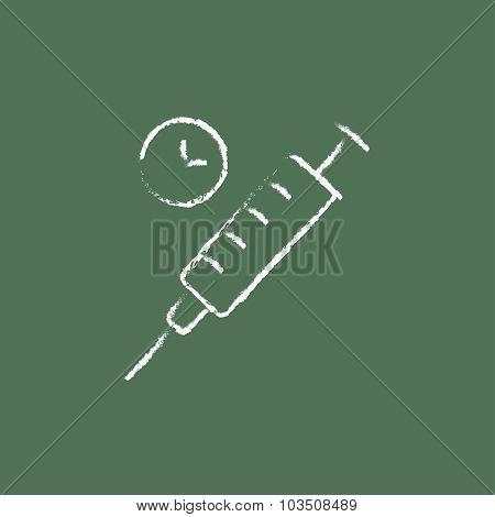 Syringe hand drawn in chalk on a blackboard vector white icon isolated on a green background.