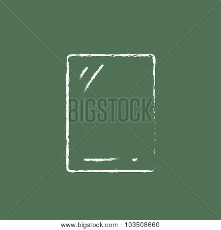 Touch screen tablet hand drawn in chalk on a blackboard vector white icon isolated on a green background.