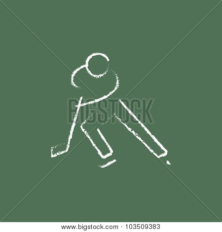 Hockey player hand drawn in chalk on a blackboard vector white icon isolated on a green background.