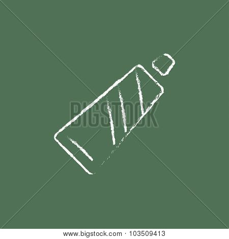Tube of toothpaste hand drawn in chalk on a blackboard vector white icon isolated on a green background.