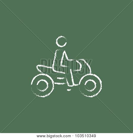 Rider on a motorcycle hand drawn in chalk on a blackboard vector white icon isolated on a green background.