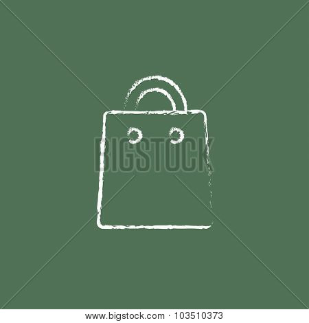 Shopping bag hand drawn in chalk on a blackboard vector white icon isolated on a green background.