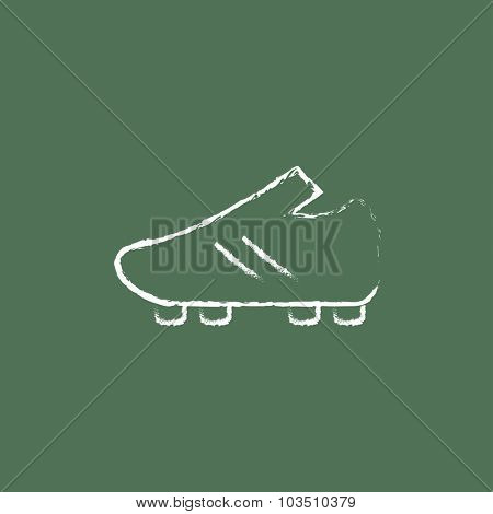 Football boot hand drawn in chalk on a blackboard vector white icon isolated on a green background.