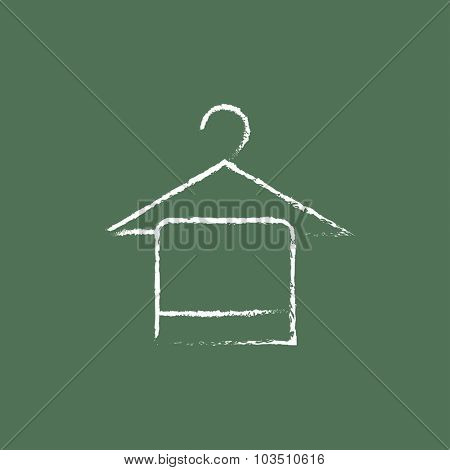 Towel on hanger hand drawn in chalk on a blackboard vector white icon isolated on a green background.