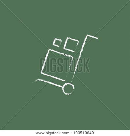 Shopping handling trolley hand drawn in chalk on a blackboard vector white icon isolated on a green background.